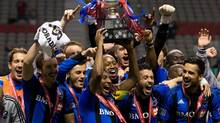 Montreal Impact's Patrice Bernier, centre, hoists the Voyageurs Cup as he and his teammates celebrate after winning the Canadian soccer Championship over the Vancouver Whitecaps in Vancouver, B.C., on Wednesday May 29, 2013. (DARRYL DYCK/THE CANADIAN PRESS)