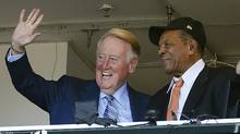 Dodgers announcer Vin Scully waves to fans alongside Hall of Famer Willie Mays during the fourth inning of a baseball game between the San Francisco Giants and the Los Angeles Dodgers in San Francisco, Sunday, Oct. 2, 2016. (AP Photo/Tony Avelar) (Tony Avelar/AP)
