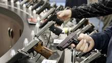 National Rifle Association members check out hand guns at the organization's May, 2006, convention in Milwaukee. (JEFF HAYNES/AFP/Getty Images)