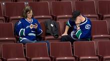Vancouver Canucks fans sit in the stands after the team gave up seven goals to the New York Islanders in the third period and lost 7-4 during an NHL hockey game in Vancouver, B.C., on Monday March 10, 2014. (The Canadian Press)