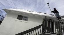 A contractor removes ice and snow from the roof of a house in Quebec. (Christinne Muschi/christinne muschi)