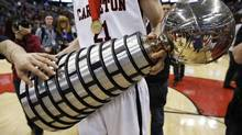 Carleton University's Cameron Smythe holds the W. P. McGee Trophy while celebrating his team's win over the University of Ottawa during their Canadian Inter-university Sport gold medal basketball game in Ottawa on March 9, 2014. (BLAIR GABLE/REUTERS)