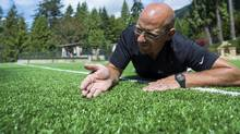 Shaun Hunt, owner of Bella Turf, inspects a West Vancouver home's artificial turf. (Jimmy Jeong for the globe and mail)