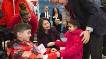 John McCallum, Minister of Immigration, Refugees and Citizenship, right, and Maryam Monsef, Member of the Cabinet Ad Hoc Committee on Refugees and Minister of Democratic Institutions, centre, welcome Syrian refugees at Pearson International Airport. (Nathan Denette/THE CANADIAN PRESS)