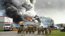 Firefighters gather at the scene of an explosion at the B.E.M. fireworks factory Thursday, June 20, 2013 in Coteau-du-Lac, Que. Two people were killed in a massive explosion at a fireworks warehouse that rattled homes and sent up a cloud of smoke that could be seen for kilometres outside Montreal. (Stephane Brunet/THE CANADIAN PRESS)