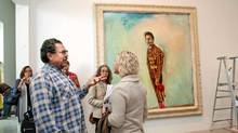 """Artist and filmmaker Julian Schnabel talks with visitors to his show """"Julian Schnabel: Art and Film"""" at the Art Gallery of Ontario in Toronto. (Della Rollins/The Globe and Mail)"""