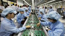 Workers assemble components at a Celestica factory in the southern China city of Dongguan. (Vincent Yu)