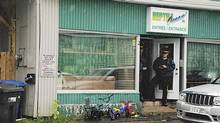 Police stand in front of the Reptile Ocean store in Campbellton, N.B. on Aug. 5, 2013 after an incident in which an African rock python escaped its enclosure, got into the apartment's ventilation system and apparently strangled two young boys as they slept. (Tim Jaques/The Tribune/Telegraph Journal/REUTERS)