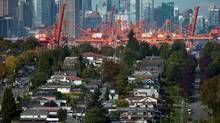 Cranes at Port Metro Vancouver are seen in the distance behind houses in east Vancouver. (DARRYL DYCK For The Globe and Mail)