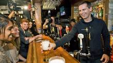 Ontario Liberal Leader Dalton McGuinty serves a pint after speaking about his party's plans for post-secondary education at a Toronto pub on Sept. 25, 2011. (Aaron Vincent Elkaim/THE CANADIAN PRESS)