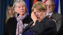 Nicole Paul, right, who is the mother of Canadian Greenpeace activists Alexandre Paul, wipes away tears as she is comforted by Patti Stirling, sister of Canadian Greenpeace activist Paul Ruzycki, as they take part in a press conference on Parliament Hill in Ottawa on Oct. 30, 2013, regarding the detention of their family members in Russia. (SEAN KILPATRICK/THE CANADIAN PRESS)