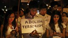 Students in Mumbai, India, attend a candle march Monday in memory of victims of last week's attack on a Pakistani school in Peshawar. (Rafiq Maqbool/AP)