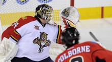 Florida Panthers goalie Tim Thomas, left, is scored on by Calgary Flames' Joe Colborne during second period NHL action in Calgary, Alta., Friday, November 22, 2013. (LARRY MACDOUGAL/THE CANADIAN PRESS)