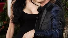 "Mick Jagger, nominated for a Golden Globe for his music in ""Hotel Rwanda"" arrives with L'Wren Scott for the 62nd Annual Golden Globe Awards on Sunday, Jan. 16, 2005, in Beverly Hills, Calif (KEVORK DJANSEZIAN/AP)"