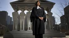 "Sharon Jeethan, a lawyer at the Toronto firm of Derstine Penman LLP, stands in front of the ""Pillars of Justice"" in Toronto on Feb. 6, 2013. Ms. Jeethan says she has grown used to hearing her profession derided whenever lawyers are mentioned at social events. (PETER POWER/THE GLOBE AND MAIL)"
