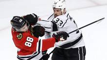Los Angeles Kings defenseman Willie Mitchell challenges Chicago Blackhawks right wing Patrick Kane (Charles Rex Arbogast/AP)