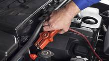 Mechanic is connecting a booster-cable to the battery in order to jump-start a car credit: istockphoto