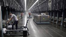 Workers and robots labour side-by-side at a textile factory in Yadkinville, N.C. (Chuck Burton/The Associated Press)