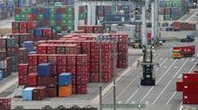 In this June 11, 2009, file photo a lift truck goes by containers at a wharf in Yokohama near Tokyo, Japan (Koji Sasahara)