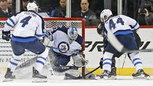 Winnipeg Jets goalie Connor Hellebuyck keeps his eye on the puck as it edges near the post during the third period of an NHL hockey game against the New York Islanders, on March 16, 2017, in New York. (Kathy Willens/AP)