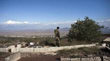 "An Israeli soldier stands in an abandoned military outpost overlooking the ceasefire line between Israel and Syria on the Israeli-occupied Golan Heights November 13, 2012. Israel's army fired tank shells into Syria on Monday and scored ""direct hits"" in response to a Syrian mortar shell that struck the Israeli-occupied Golan Heights, the Israeli military said in a statement. It was the second time in as many days that Israel had fired across the disengagement line drawn at the end of a war in 1973, underscoring international fears that Syria's civil war could ignite a broader regional conflict. (NIR ELIAS/REUTERS)"