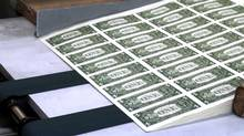 Sheets of U.S. one dollar bills roll off the press at the Bureau of Printing and Engraving in Washington, D.C.