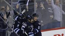 Winnipeg Jets' Evander Kane (9), Mark Stuart (5) and Mark Scheifele (55) celebrate Kane's goal against the Los Angeles Kings during first period NHL action in Winnipeg on Friday, October 4, 2013. (JOHN WOODS/THE CANADIAN PRESS)