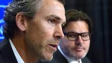 Trevor Linden, left, speaks as Vancouver Canucks owner Francesco Aquilini looks on at a press conference in Vancouver on Wednesday, April 9, 2014. (The Canadian Press)