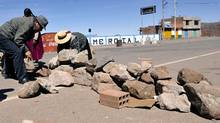 Locals block the road to the Desaguadero international bridge, linking Bolivia and Peru, during a protest against a mining project by a Canadian subsidiary, on May 16, 2011, in Desaguadero, 112 km west of La Paz. Both in Bolivia and in the Peruvian southeastern department of Puno, locals held the road blockade stating that the mining project will pollute the Desaguadero river and the Titicaca Lake. (AIZAR RALDES/AFP/Getty Images/AIZAR RALDES/AFP/Getty Images)