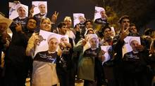 In this photo released by the Iranian Students News Agency, ISNA, Iranians hold posters of President Hassan Rouhani as they welcome Iranian nuclear negotiators upon their arrival from Geneva at the Mehrabad airport in Tehran, Sunday, Nov. 24, 2013. (Hemmat Khahi/Associated Press)