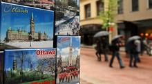 A tourist boutique displays Parliament Hill magnets as pedestrians make their way along Ottawa's Sparks Street Mall on May 16, 2011. (Sean Kilpatrick/THE CANADIAN PRESS)