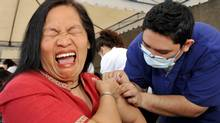 A city government employee grimaces as she receives a vaccination against ordinary seasonal flu in the financial district of Manila.