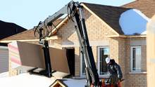 A construction worker delivers sheets of drywall to the site of a new housing development in Ottawa, in this file photo. (Sean Kilpatrick for The Globe and Mail)