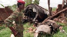 A Rwanda Patriotic Front (RPF) rebel walks by the the site of a April 6 plane crash which killed Rwanda's President Juvenal Habyarimana in this May 23, 1994 file photo in Kigali. (JEAN MARC BOUJOU/ASSOCIATED PRESS)