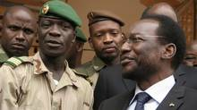 Coup leader Amadou Haya Sanogo, (C), stands with Mali's parliamentary head Dioncounda Traore, right, at junta headquarters in Kati, outside Bamako, Mali Monday, April 9, 2012. (Harouna Traore/AP)