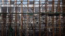 A migrant worker dismantles scaffolding on the front of a new building at a construction site in central Beijing. (DAVID GRAY/REUTERS)
