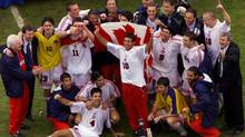 Canada's soccer team and their coaches pose for photographers as they celebrate their upset win over Colombia, 2-0, for the championship match of the Gold Cup soccer tournament Sunday, Feb. 27, 2000, at the Coliseum in Los Angeles. (KEVORK DJANSEZIAN/AP)