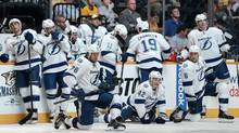 Tampa Bay Lightning players, including Pierre-Cedric Labrie (76), Dana Tyrell (42) and Sami Salo (6), of Finland, wait for the lights to come back on during a delay after they were dimmed for the National Anthem before the start of a preseason NHL hockey game against the Nashville Predators on Tuesday, Sept. 24, 2013, in Nashville, Tenn. (Associated Press)