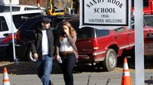 Parents walk away from the Sandy Hook Elementary School with their children following a shooting at the school, Friday, Dec. 14, 2012 in Newtown, Conn. (Frank Becerra Jr./AP)