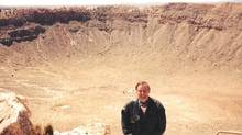 Lawrence Morley, geologist / geophysicist, stands in front of Barrington Crater in Arizona.