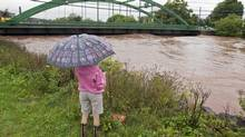 A resident watches the water as dikes on the Salmon River gave way in Truro, N.S. on Monday. (ANDREW VAUGHAN/THE CANADIAN PRESS)