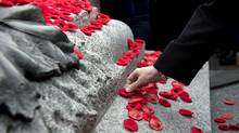 People place poppies on the Tomb of the Unknown Soldier at the National War Memorial following the Remembrance Day ceremony in Ottawa on Nov. 11, 2015. (JUSTIN TANG/THE CANADIAN PRESS)