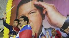 Venezuela's acting President Nicolas Maduro carries a child dressed as national hero Simon Bolivar in front of a poster of late president Hugo Chavez during a campaign rally in the state of Lara March 24, 2013 in this picture provided by the Miraflores Palace. (HANDOUT/REUTERS)