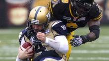 Winnipeg Blue Bombers starting quarterback Buck Pierce (left) is tackled by Hamilton Tiger Cats Renauld Williams (right) during first half CFL action in Hamilton on Saturday October 27 , 2012. (The Canadian Press)