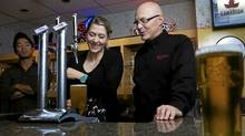 Ali Camerson receives tips on pouring beer from fellow Molson Coors employee Jeff Armstrong. (Michelle Siu/The Globe and Mail)