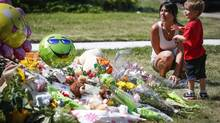 Jennifer Kohut and her son Axton, three, place flowers and a toy at an impromptu memorial for Nathan O'Brien and his grandparents, Alvin and Kathryn Liknes, at the Liknes home in Calgary, Alta., Tuesday, July 15, 2014. (Jeff McIntosh/THE CANADIAN PRESS)
