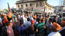 At a rally in Lucknow, BJP campaigner Abhijat Mishra, 35, (centre, white shirt with arm raised) is leading a chanting crowd trying to draw attention to their party's symbol on India's electronic voting machines, which enable the illiterate to vote by choosing between a hand for Congress, a lotus for BJP, and a bicycle for Samajwadi, among many others. (Iain Marlow for The Globe and Mail)
