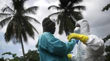 An Ebola burial team dresses in protective clothing before collecting the body of a woman, 54, from her home in the New Kru Town suburb on October 10, 2014 in Monrovia, Liberia. (John Moore/Getty Images)