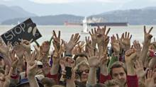 Protestors gathered on Kitsilano Beach hold up their hands to show their opposition to the Northern Gateway Pipeline and the use of oil tankers in local waters in Vancouver, British Columbia June 3, 2012. (ANDY CLARK/REUTERS)