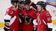 Ottawa Senators right wing Mark Stone(61), Marc Methot (3) and Erik Karlsson(65) congratulate teammate Kyle Turris on his goal during third period NHL action Sunday March 30, 2014 in Ottawa. (Adrian Wyld/THE CANADIAN PRESS)